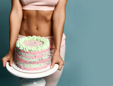 Closeup on big heavy birthday holiday cake with cream fitness woman in top bra and pants holds is carrying in hands over blue background with copy space. Figure, present, birthday party concept