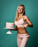 Young sexy blonde fitness woman in top bra and pants stands holding big holiday cake in hand and pointing down or at stomach. Figure, present, birthday party concept