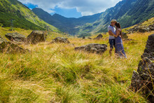 Young Couple Sitting On A Rock In Front Of The Background Of High Mountains In Romania. Woman And Man Hugging Near Transfegerasan, One Of The Most Spectacular Mountain Road, Best According To Top Gear