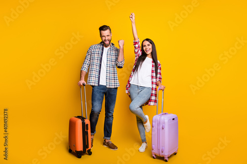 Obraz Photo portrait full body view of cheerful excited couple with suitcases isolated on vivid yellow colored background - fototapety do salonu