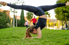 Fit Young Blonde Gymnast Girl Doing Elbow Handstand With Open Legs At The Park. Yoga Woman Gymnastics Silhouette
