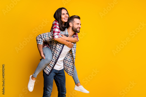 Fotografie, Obraz Portrait of lovely cheerful couple embracing piggy backing having fun isolated o