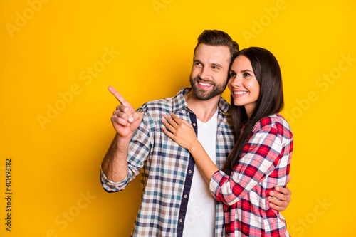 Portrait of two lovely cheerful people embracing pointing forefinger copy space Wallpaper Mural