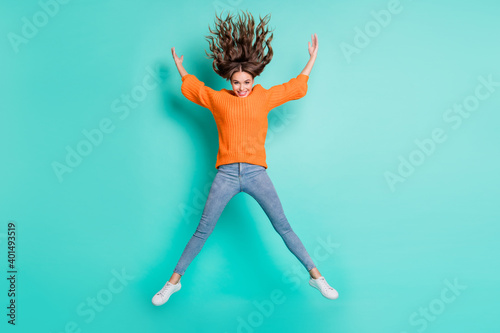 Full size photo of young lovely pretty careless carefree girl jumping in star pose with flying hair isolated on teal color background