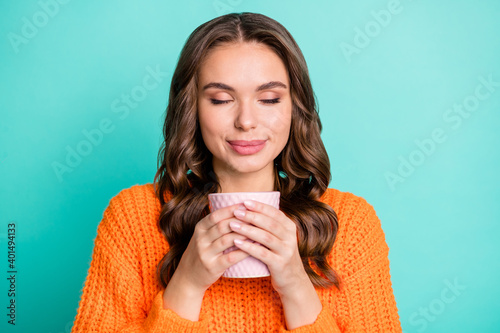 Obraz Portrait of young pretty lovely smiling girl smelling drinking tea coffee enjoying break time isolated on teal color background - fototapety do salonu