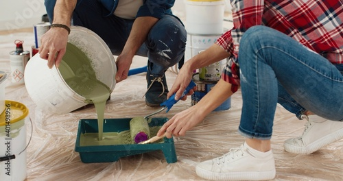Photo Close up of Caucasian happy nice married couple man and woman pouring paint and preparing for painting house