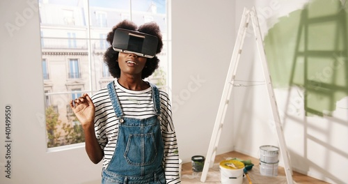 Fotografering Portrait of African American young impressed excited woman stands in room wearin