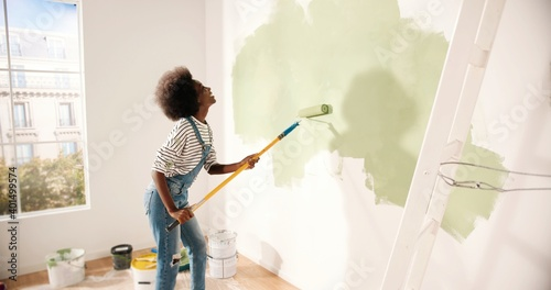 Young African American woman dancing and painting wall with roller brush while renovating apartment. Rear of female having fun redecorating home, renovating and improving Repair and decorating concept - fototapety na wymiar
