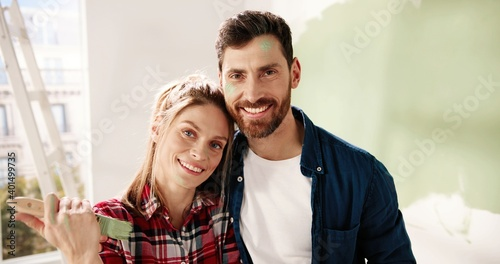 Canvas Print Close up portrait of happy young married couple wife and husband hugging, embracing, looking at camera and smiling after painting walls during home repair process