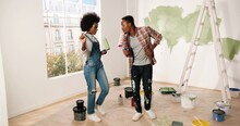 Young Cheerful African American Couple Man And Woman Hugging And Embracing In Good Mood Smiling In Apartment During Home Repair Works. Wife And Husband Renovating House. Remodeling Concept