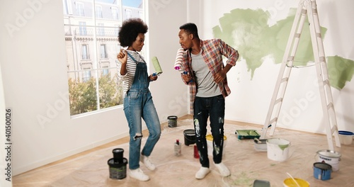 Fotografie, Obraz Young cheerful African American couple man and woman hugging and embracing in good mood smiling in apartment during home repair works