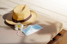 Preparing Beach Stuff Straw Hat With Surgical Face Mask On Chair Lounger With Sun Light.