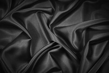 Abstract Black Background. Black Silk Satin Fabric Texture Background. Beautiful Soft Folds On Shiny Fabric. Black Elegant Background For Your Design.