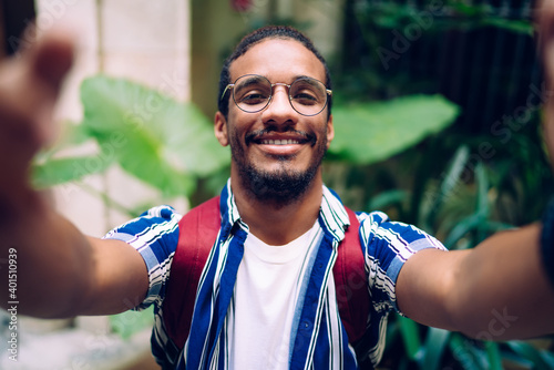 Fotografie, Obraz Self portrait of happy ethnic man in eyeglasses on street with plants