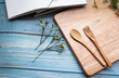 Wooden fork and spoon put  on timber board beside beautiful small flower