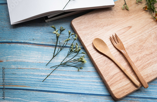 Obraz Wooden fork and spoon put  on timber board beside beautiful small flower - fototapety do salonu