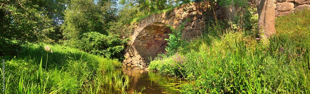 Fototapeta Small medieval stone bridge across the Vilce river in a green summer forest. Latvia, Europe. Idyllic landscape. Panoramic view. Travel destinations, landmarks, history, past, traditional architecture