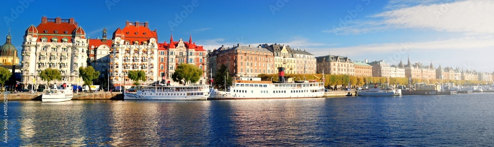 Fototapeta Passenger ships moored to a pier in a city centre of Stockholm, Sweden. Golden trees, clear blue sky. Panoramic autumn cityscape. Traveling, national landmarks, sightseeing theme