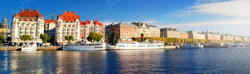Obraz Passenger ships moored to a pier in a city centre of Stockholm, Sweden. Golden trees, clear blue sky. Panoramic autumn cityscape. Traveling, national landmarks, sightseeing theme - fototapety do salonu