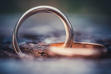 Close-up Of A Ring With Three Rings On Wooden Background. Wedding Jewelry In Gold, White Gold And Rose Gold. Macro Shot With Selective Focus