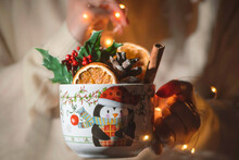 A Young Woman Holds Large Mug With Full Of Christmas Flower, Oranges, Cinnamon Sticks And Pine Cone With Lights , Close Up, Still Life Photography
