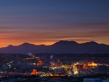 Factories And Mountain Silhouettes At Dawn