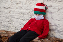 A Child In A Medical Mask Wearing A Santa Claus Hat Due To The Coronavirus Pandemic. Sad Little Boy Wearing A Christmas Hat During The Coronavirus Epidemic.
