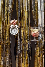Feminine Hand Holds Clock Showing Almost Midnight And A Glass Of Champagne