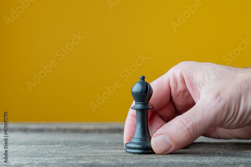 Foto Placing black chess piece of bishop on wooden boards