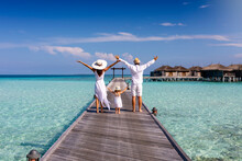 A Happy Family In White Summer Clothing On Vacation Walks Along A Wooden Pier Over Tropical, Turquoise Ocean In The Maldives, Indian Ocean