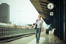 Blonde Caucasian Woman Waiting At The Railway Station Carrying Bag.