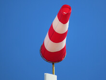 Windsock Indicator Of Wind On Runway Airport. Wind Cone Indicating Wind Direction And Force. Horizontally Flying Windsock (wind Vane) With Blue Sky In The Background.