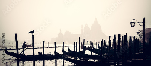 Romantic Italian city of Venice, a World Heritage Site: traditional Venetian wooden boats, gondolier and Roman Catholic church Basilica di Santa Maria della Salute in the misty background Fototapet