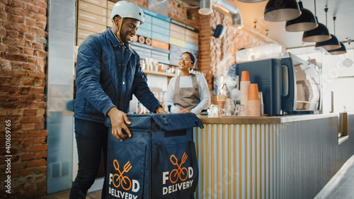 Fototapeta Beautiful Happy Latin Barista Serves Order of a Food Delivery Courier. Delivery Guy Puts Food in His Hot Thermal Insulated Bag and Closes it. Sunny and Bright Modern Cafe. obraz