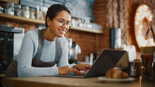 Young And Beautiful Latina Coffee Shop Owner Is Working On Laptop Computer And Checking Inventory In A Cozy Cafe. Successful Restaurant Manager Browsing Internet And Accepting Online Take Away Orders.