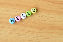 Selective Focus With Blurred Effect Of Colorful Alphabet Beads With Text HELLO Over Wooden Background.