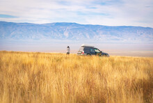 Background View Of Beautiful VAshlovani Meadow Panorama With 4Wd Standing In Middle With Woman Standing And Enjoy Views.Travel Destination Georgia.
