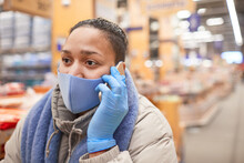 Young Woman In Protective Mask Talking On Mobile Phone While Standing In Supermarket