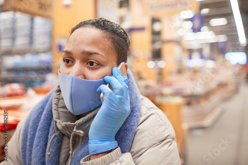 Photo Young woman in protective mask talking on mobile phone while standing in superma