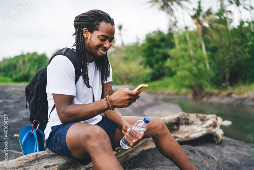 Smiling black man using smartphone in tropical forest near river Wallpaper Mural