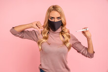 Sick Sad Young Woman In Pink Blouse, Sterile Face Mask To Safe From Coronavirus Virus Covid-19 During Pandemic Quarantine Hold And Pointing Finger On Thermometer Isolated On Pastel Pink Background.