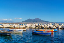 View Of Volcano Vesuvius View From Seafront With Colorful Boats In The Foreground, Naples, Campania, Italy