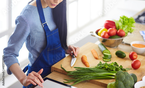Papel de parede Young woman cutting vegetables in kitchen at home