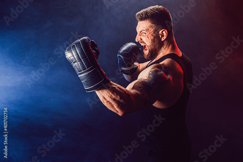 Fototapeta Bearded tattooed sportsman muay thai boxer in black undershirt and boxing gloves fighting on dark background with smoke