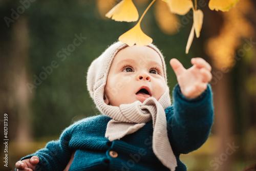 Photo Bebé intentando de coger unas hojas de un árbol con gorro en invierno