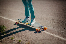 Legs Of Woman With Jeans On Skateboard On The Road