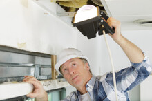 Builder Inspecting Roof With A Lamp