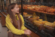 Excited little baker girl examining bakery store retail display cheerfully, copy space