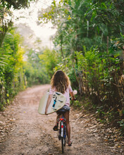Woman On A Bicycle With Surfboard On Rural Road With Green Trees Along. Tropical Green. Sport Lifestyle Concept.