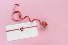 A Letter Card And Red Ribbon With Polka Dots On Pink Background